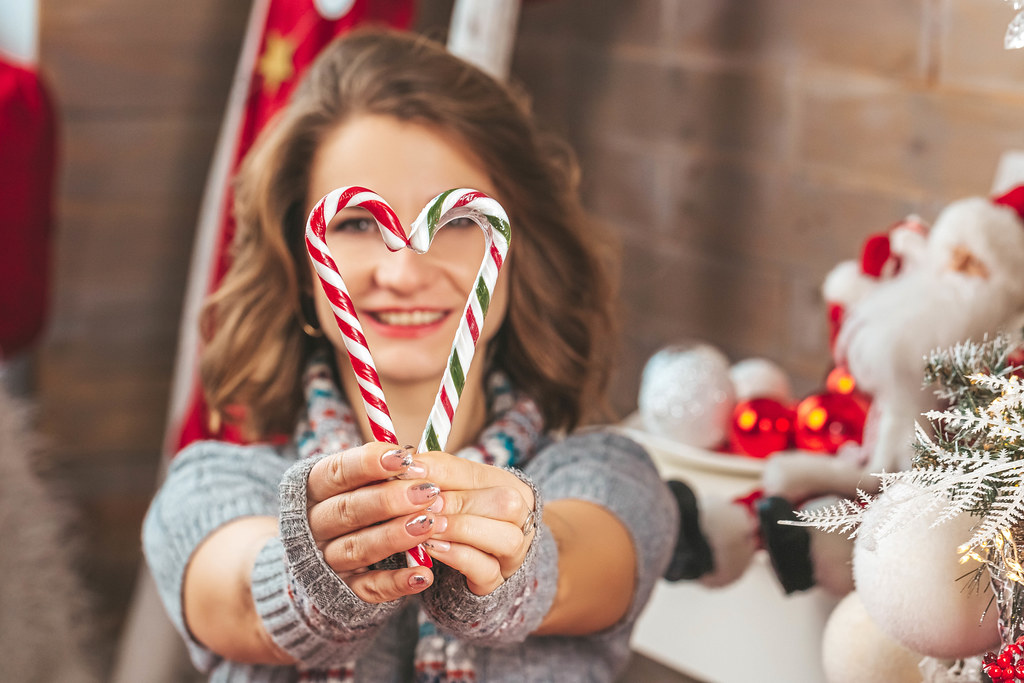 Close-up, a heart made of candy cane in the hands of a girl