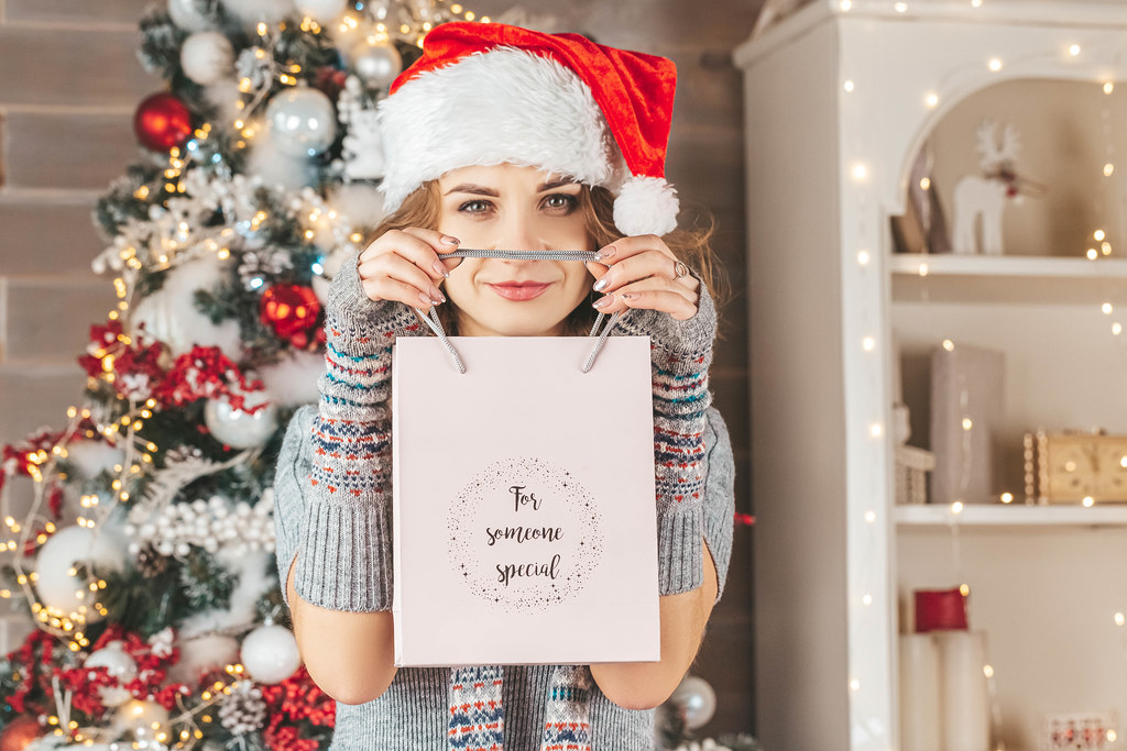 Gift bag in the hands of a woman in a santa hat