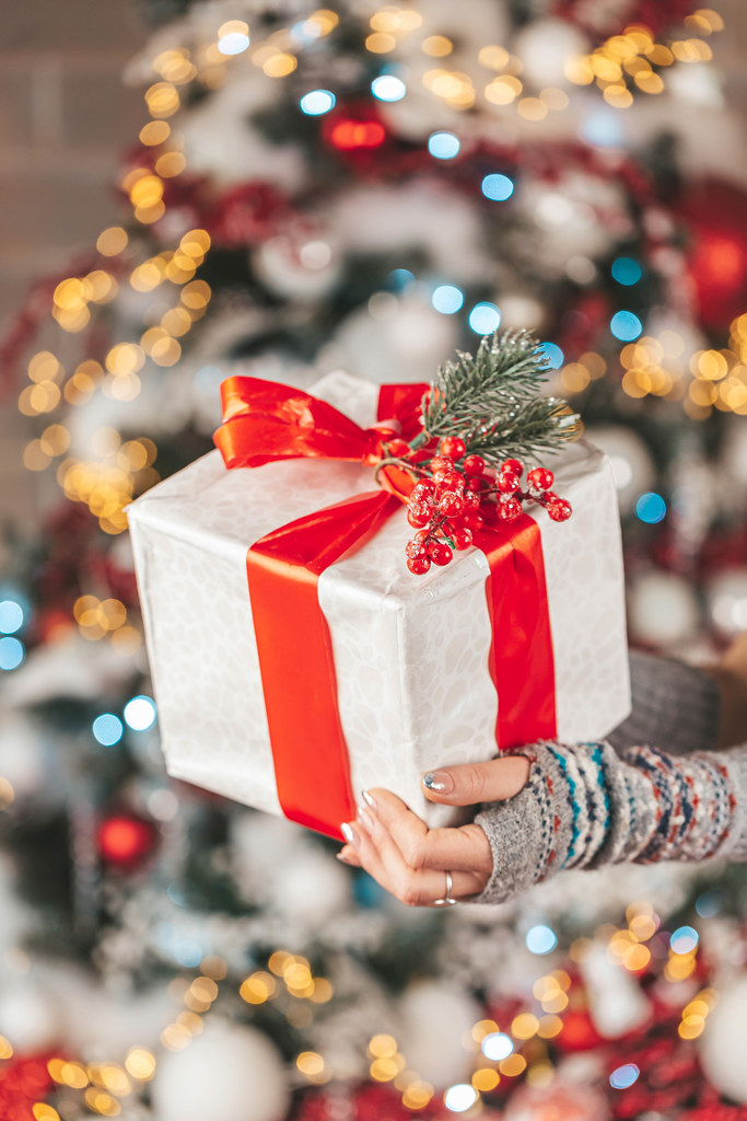 Christmas gift with red ribbon in hands on multicolored bokeh background