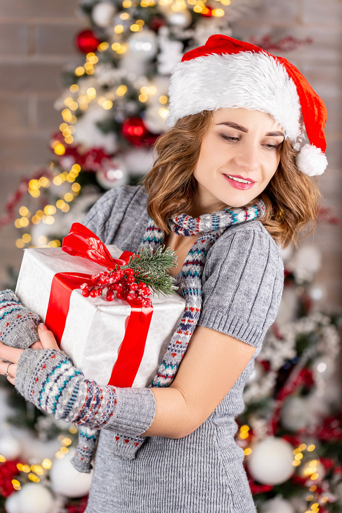 A woman with a gift in her hands in a dress, scarf, and santa hat on the background of a christmas tree