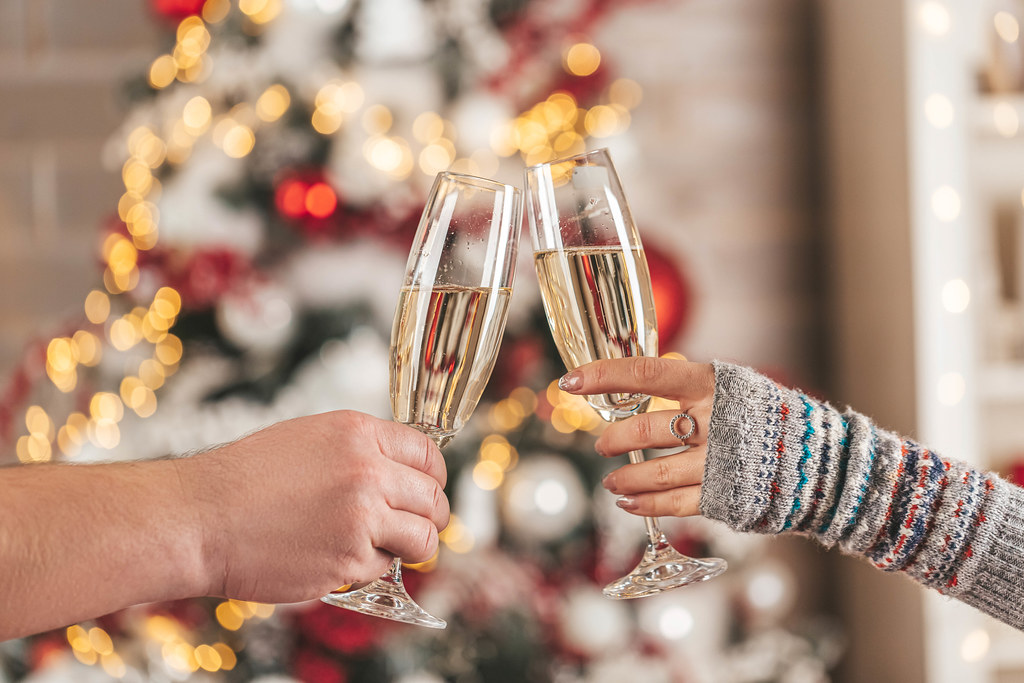 Two glasses of champagne in the hands of a man and a woman on a blurred background of a decorated christmas tree