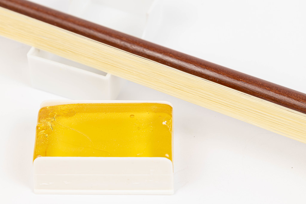 Wooden Fiddle Bow with Rosin above white background