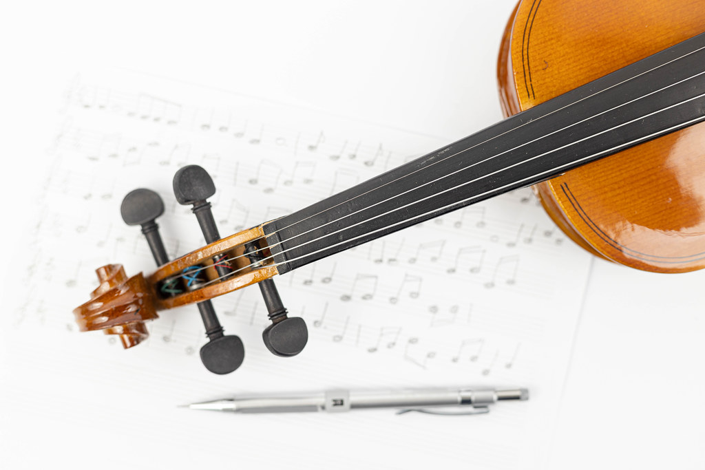 Wooden Violin Neck with Notes on the sheet music and Pencil
