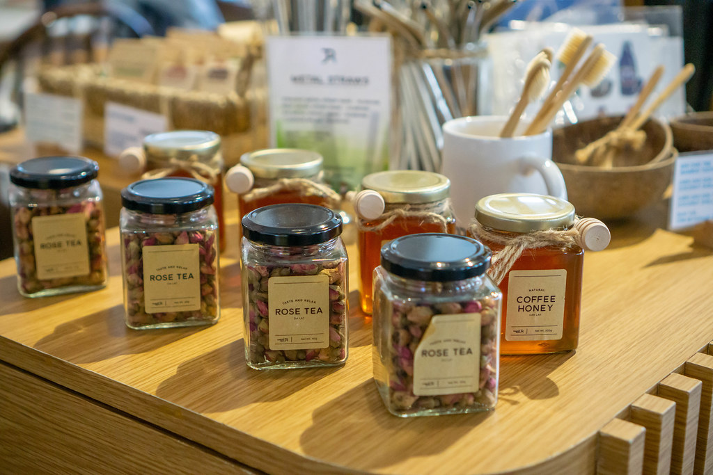 Rose Tea and Coffee Honey in Glass Jars with Bamboo Toothbrushes and Metal Straws in the Background on a Sale Table in a Cafe