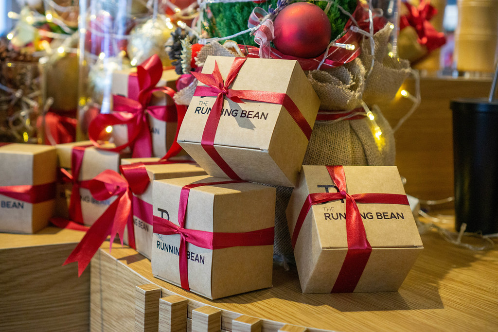 Christmas Gift Boxes with Red Ribbon on a Wooden Table with Decorated Christmas Tree and other Decorations in the Background