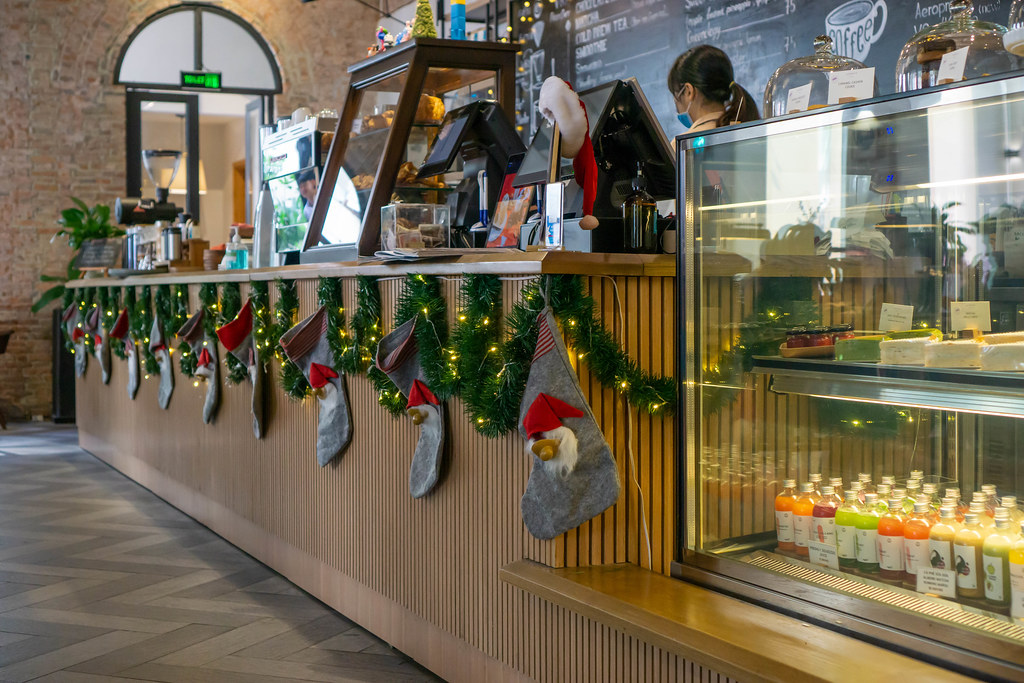 Christmas Decorations with String Lights, Stockings and Garlands on a Cafe Counter with Display Fridge and Cashier