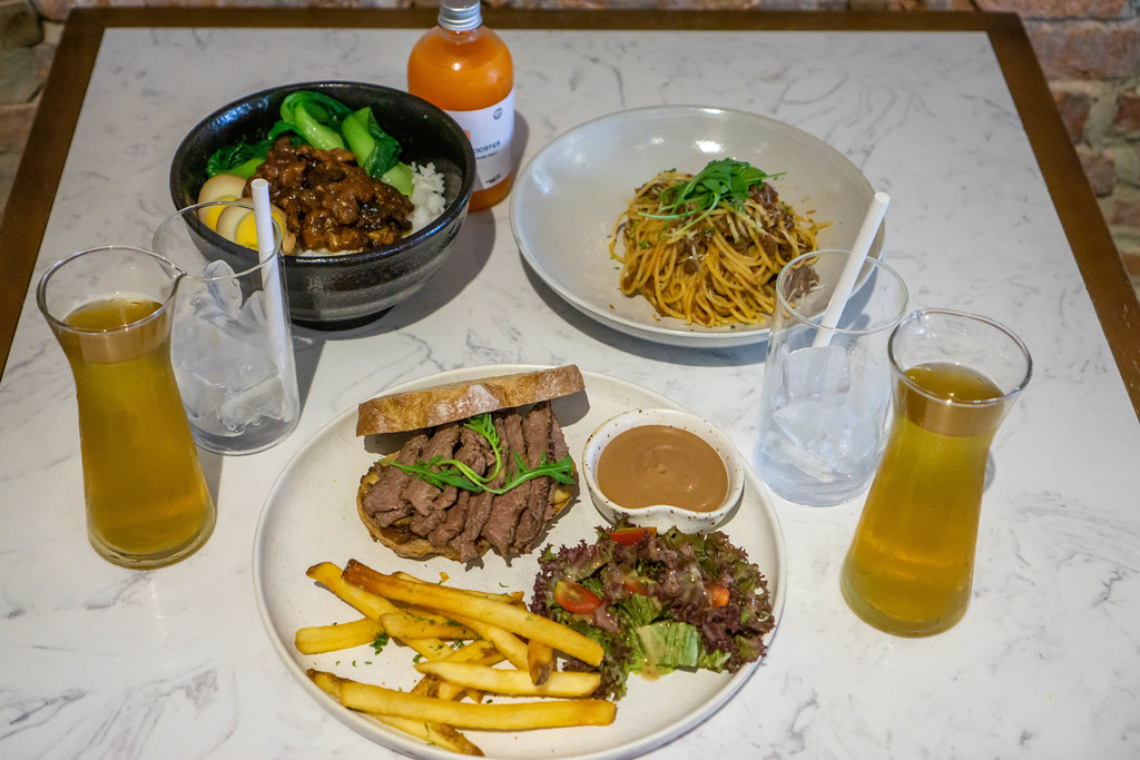 Steak Sandwich with French Fries and Salad, Spaghetti Bolognese, Taiwanese Braised Pork Bowl, Iced Tea and Fresh Juice on a Restaurant Table