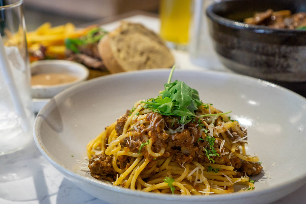 Close Up Food Photo of Spaghetti Bolognese with Tomato and Minced Meat topped with Grated Cheese and Arugula with other Dishes in the Background