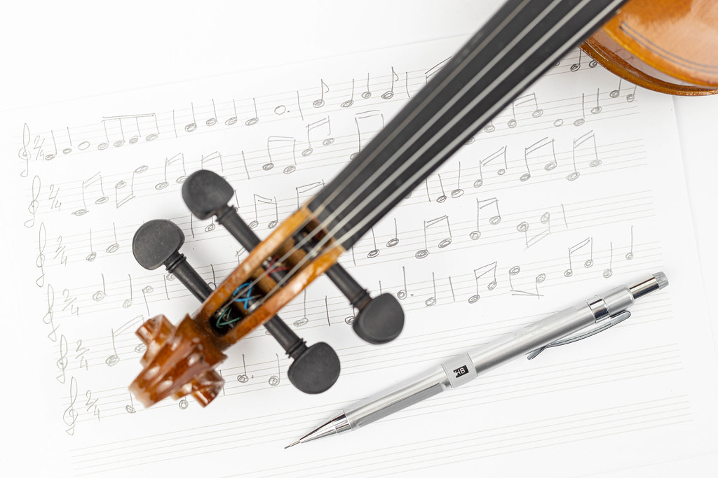 Wooden Violin Neck with Notes on the sheet music and Pen above white background