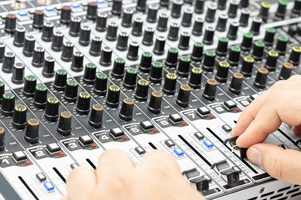 Studio engineer mixing with hands on Studio Mixer