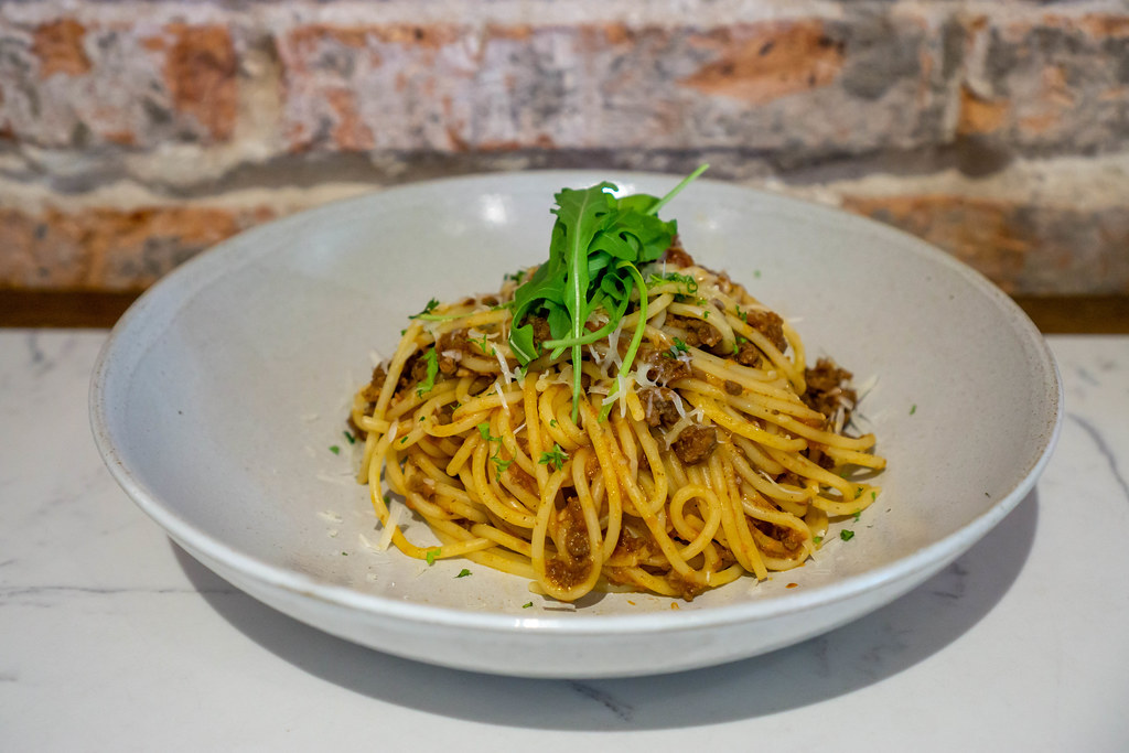 Food Photo of Plate of Spaghetti Bolognese with Grated Cheese and Arugula in a Restaurant