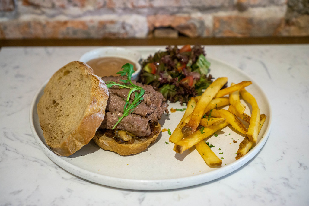 Close Up Food Photo of Slices of Steak with Caramelized Onions on Bread Slices with French Fries and Salad on a White Ceramic Plate