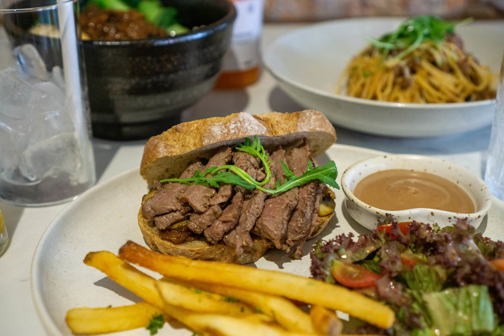 Close Up Photo of Food Plate with Steak Slices on Bread Slice with Caramelized Onions, French Fries and Salad as Side Dish and other Dishes in the Background