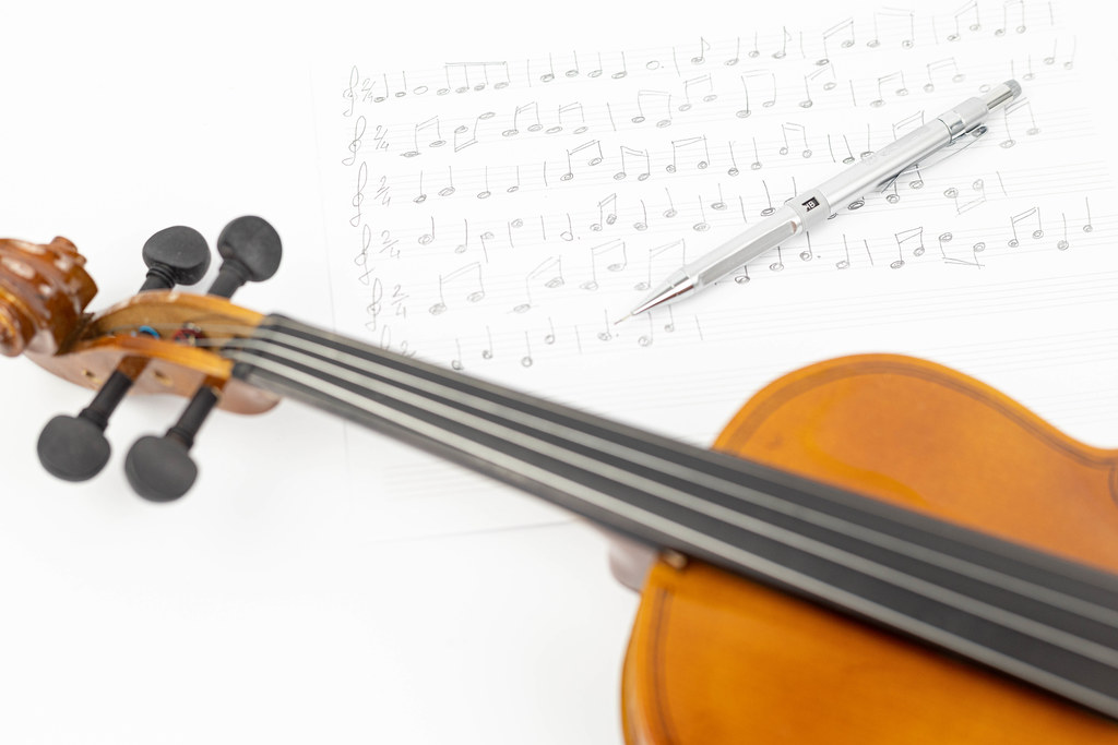 Wooden Violin with Notes on the sheet music above white