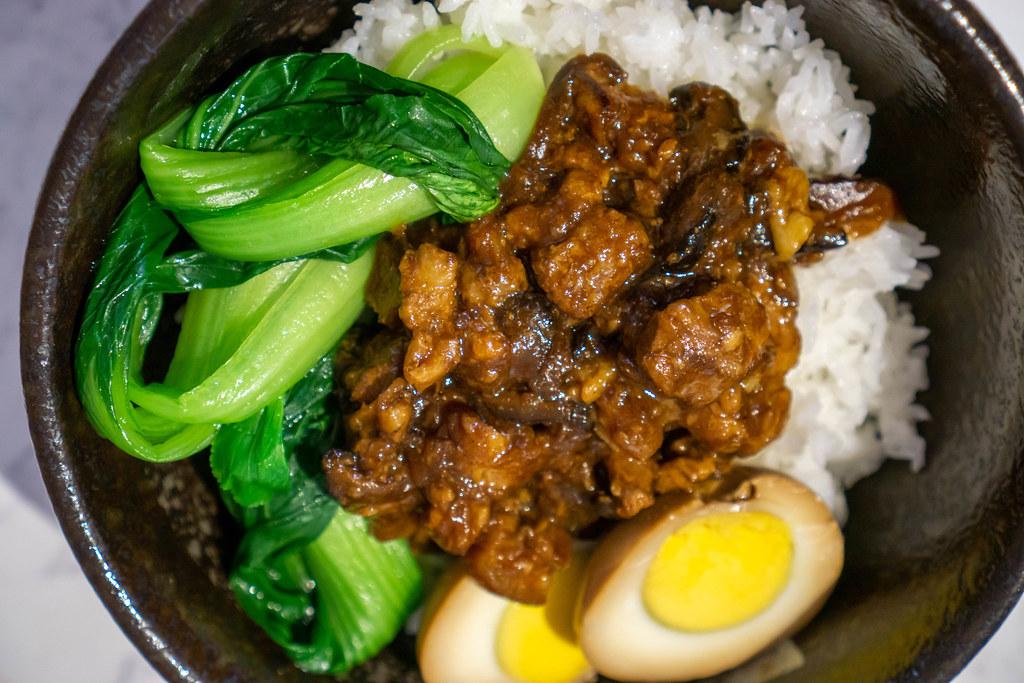 Geschmortes Schweinefleisch, Entenei, Bok Choy Gemüse und Reis als Taiwainesische Reis-Bowl in einer schwarzen Keramikschale Nahaufnahme