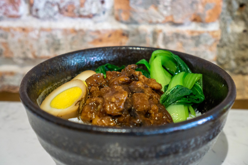 Close Up Food Photo of Taiwanese Braised Pork with Duck Egg, Bok Choy and White Rice in a Black Ceramic Bowl
