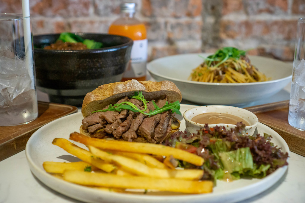 Sandwich with Beef Steak Slices, Arugula and Caramelized Onions with Spaghetti Bolognese, Rice Bowl and Drinks in the Background