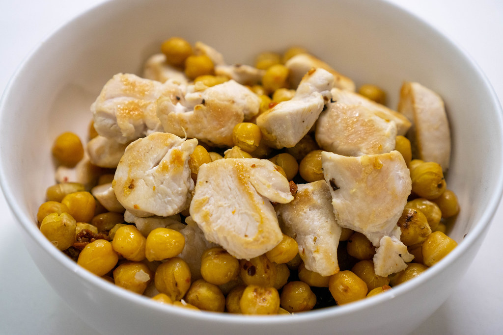 Close Up Food Photo of Grilled Chicken Breast with Fried Chickpeas in a White Ceramic Bowl
