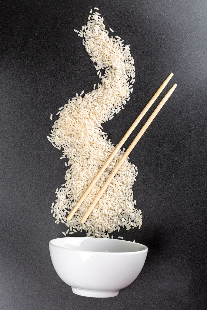 Scattered raw rice with wooden chopsticks and white bowl on black background