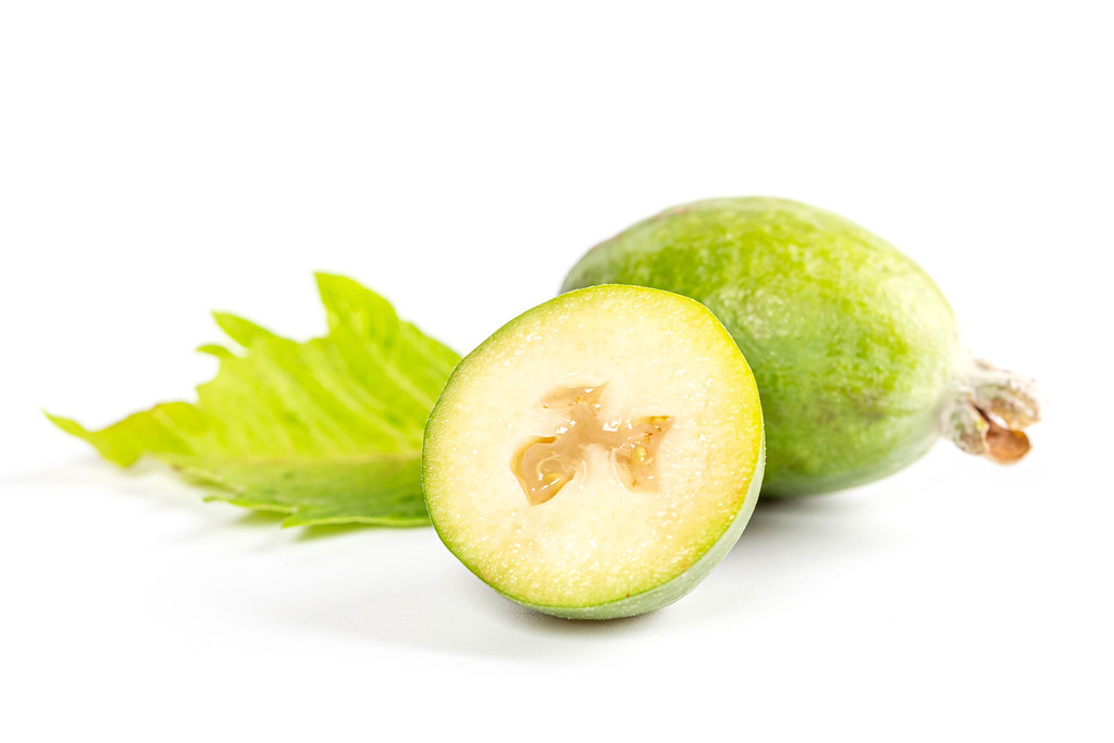 Whole and half feijoa fruit with green leaf