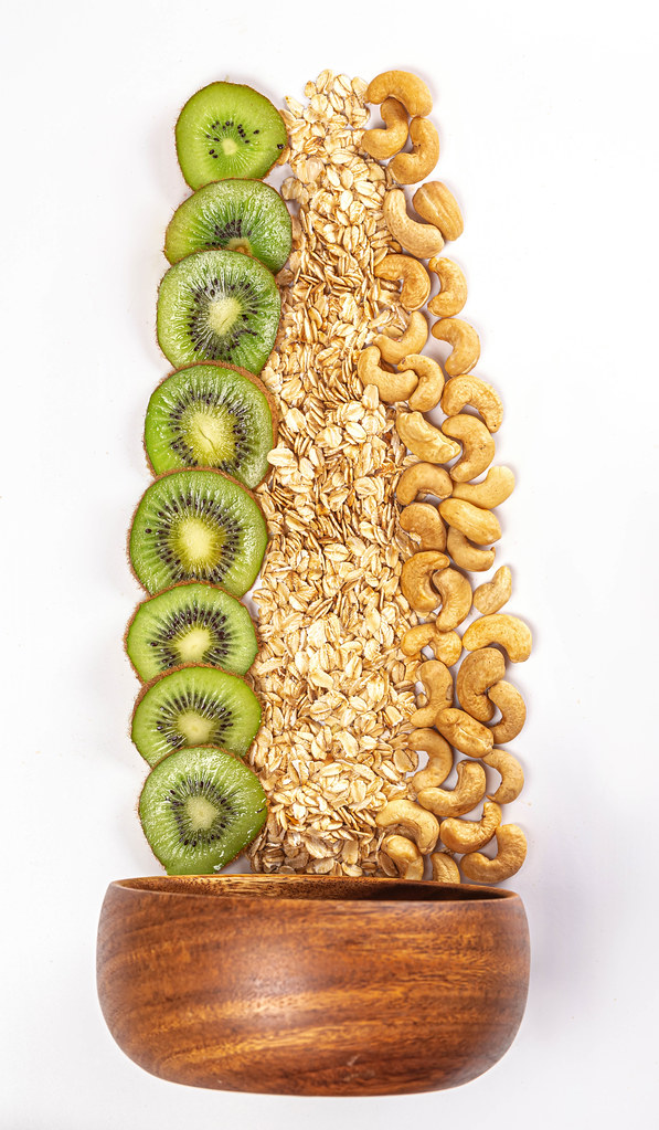 Wooden bowl with oatmeal, kiwi and cashew nuts, ingredients for a healthy breakfast