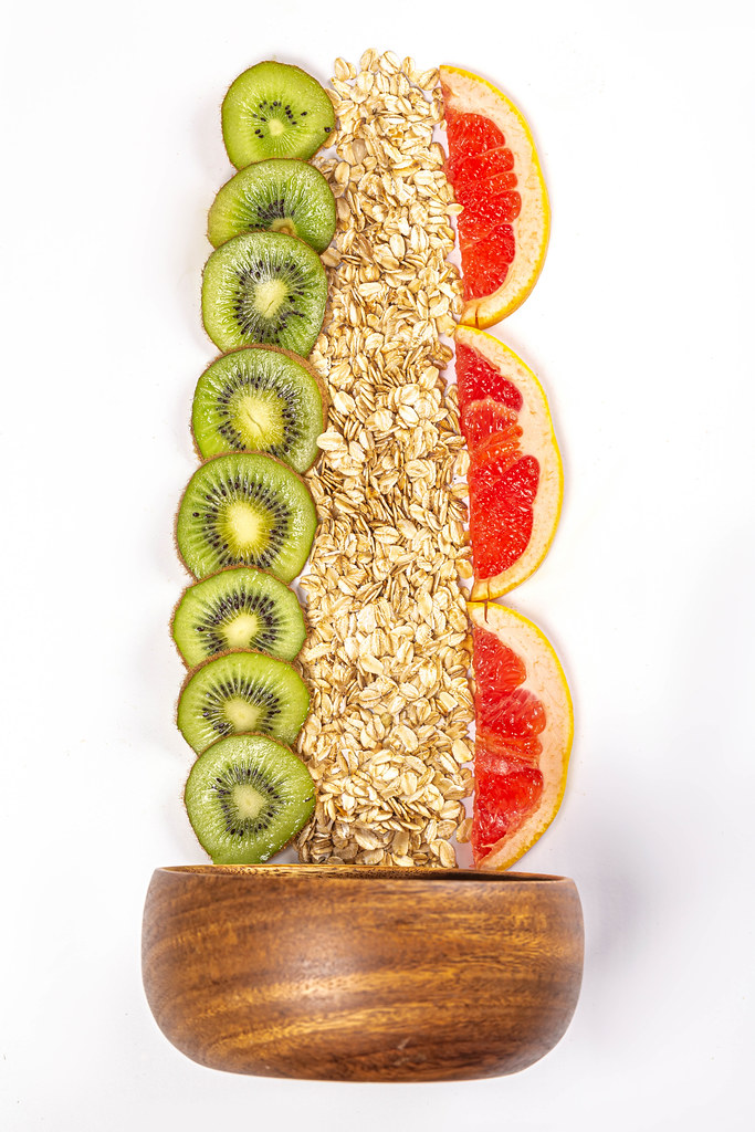 Oat flakes with fresh kiwi and grapefruit slices on white background with wooden bowl
