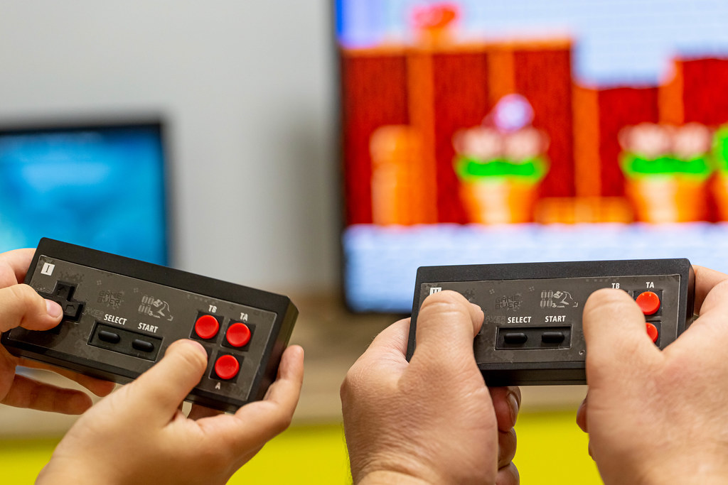 Father and son hands with joysticks play an eight-bit game
