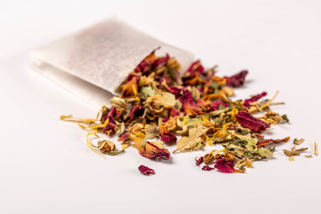 Close-up of green tea sprinkled with flowers petals and tea bag