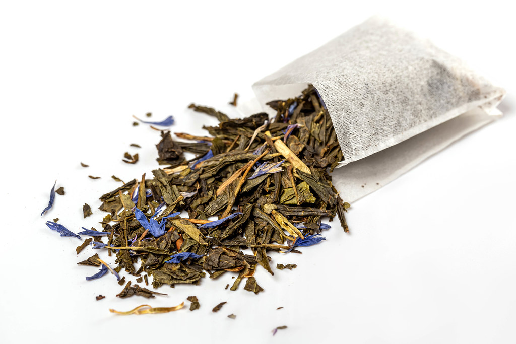 Tea bag with scattered green tea and blue flowers, close up