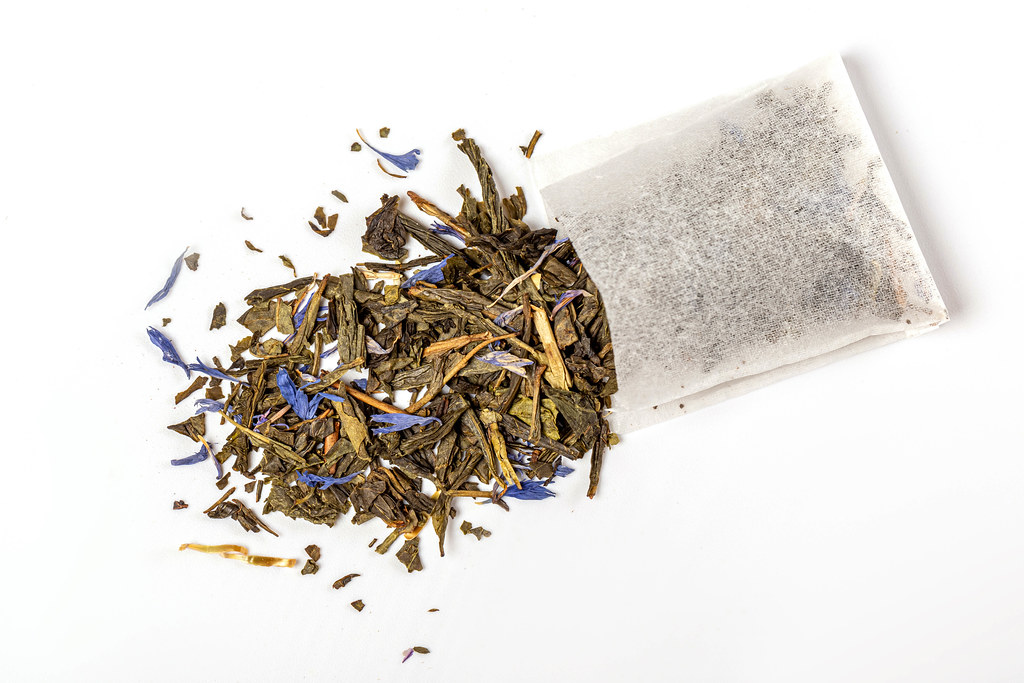 Top view, tea bag with scattered green tea and blue petals