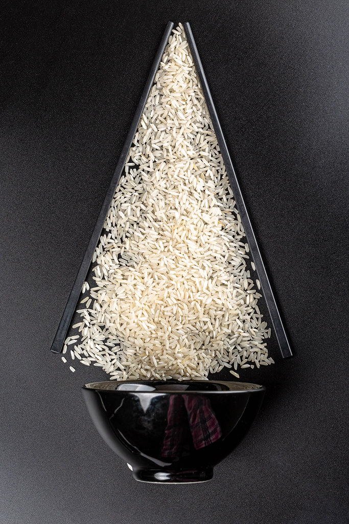 Bowl with raw rice and chopsticks on a dark background, top view