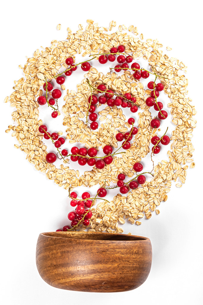 Top view, spiral with oatmeal and red currant berries with wooden bowl