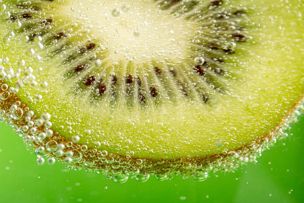 Green fruit background with kiwi slice and bubbles