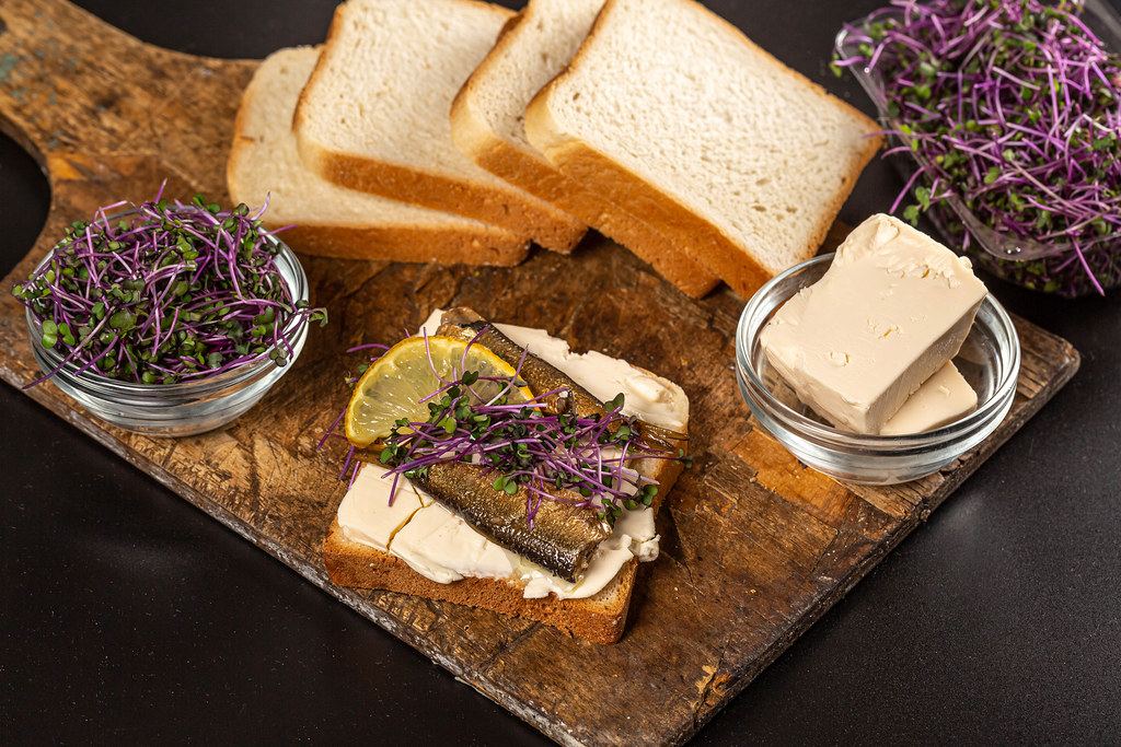 Sandwich with sprats and microgreens on an old wooden board