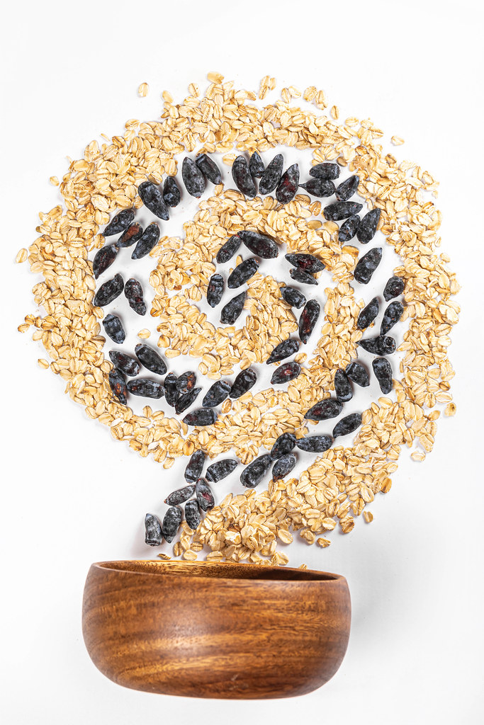 Spiral with oatmeal and honeysuckle berries with a wooden bowl, diet food