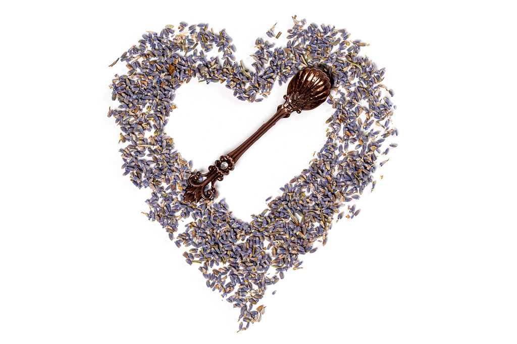 Top view, heart made of lavender flowers on white with teaspoon
