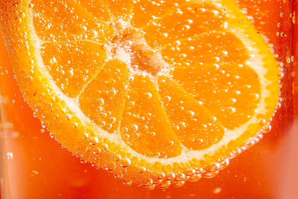 Orange background with fresh tangerine and soda bubbles