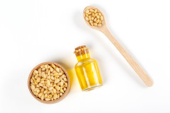 Top view, pine nut oil in bottle with pine nuts in w…
