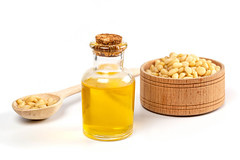 Oil in a bottle with pine nuts in a wooden spoon and…