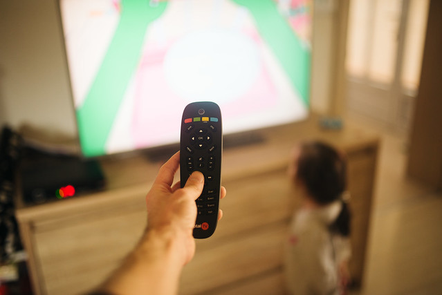 Man and little girl at home family time standing in living room near TV. Father holding remote controller closeup.