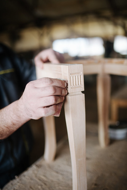 Carpenter sandpapering chair legs.