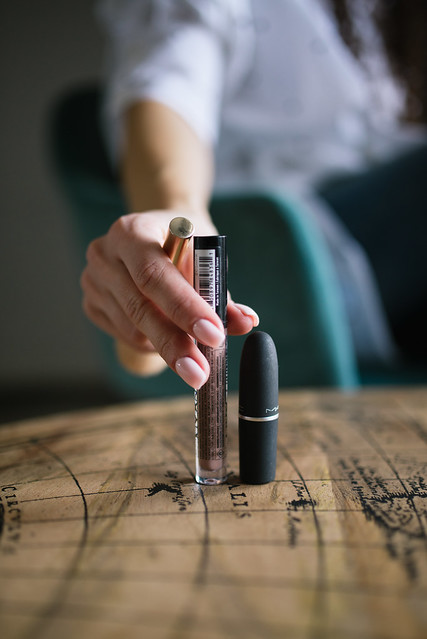 Close-up of woman's hand reaching for lipstick on the table