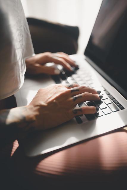 Tattooed fingers on laptop.