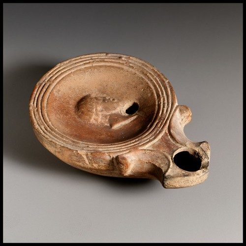 Roman terracotta lamp with discus bearing a human head in high relief