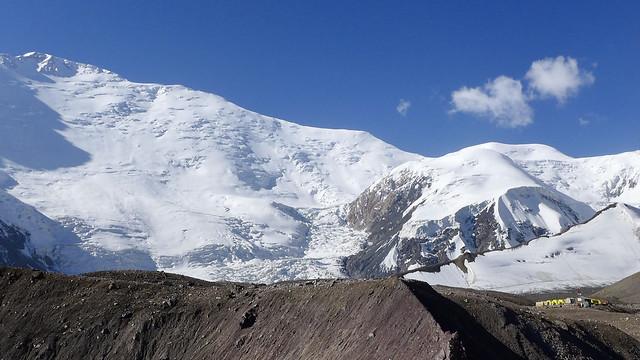 Der Pik Lenin (Gipfel links oben) mit dem Zelten des vorgeschobenen Basislagers. Der Anstieg führt oberhalb des Eisbruchs nach recht an den Grat und über diesen zum Gipfel.
