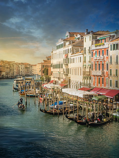 Beautiful sunrise in Venice, views of one of its famous canals crisscrossed by gondolas.